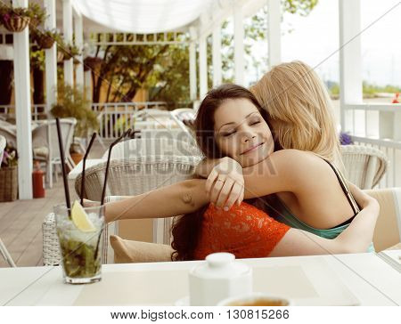 portrait of two pretty modern real girl friends in cafe open air interior drinking and talking, having chat and coctail, lifestyle friendship concept