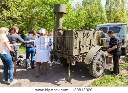 SAMARA RUSSIA - MAY 9 2016: Traditional distribution of cooked buckwheat porridge on the field kitchen in a city park on a holiday