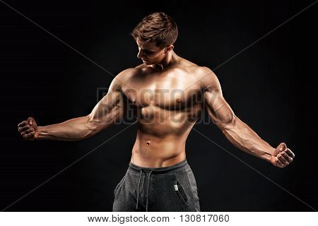 Stunning muscular man showing six pack abs, perfect abs, shoulders, biceps, triceps and chest on black background.