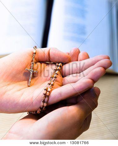 Creyente cristiano orar a Dios con el Rosario en la mano.