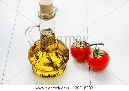 Bottle of olive oil with herbs and two red tomatoes on white wooden table