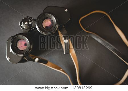 Old binoculars with strap on black background. Top view