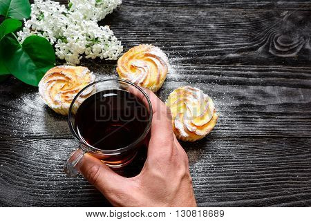 Black tea in a glass cup with cupcakes