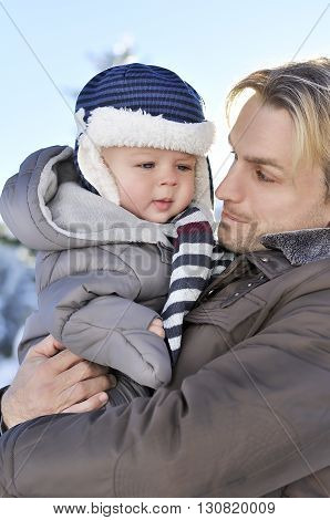 Happy family. Portrait of young father in a winter park with his sweet baby boy