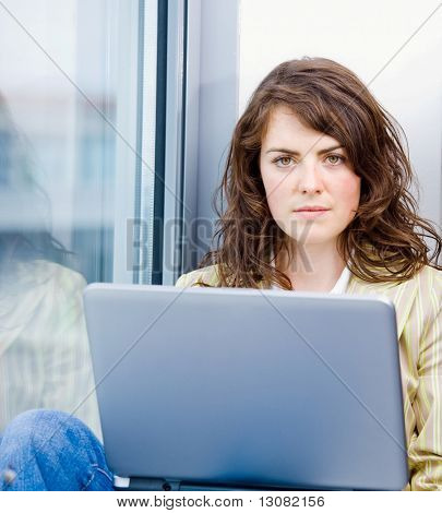 Portrait of young attractive businesswoman sitting in office window and wokring on laptop computer, lloking at camera.