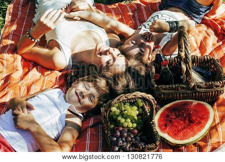 cute happy family on picnic laying on green grass mother and kids, warm summer vacations close up, brother and sister together smiling