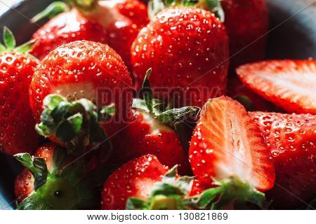 Bunch of fresh strawberries halves and wholes. With green strawberry stalks. Fresh, tasty red strawberry, extreme close-up.