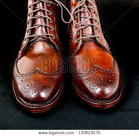 Wingtip dark chili brown dress boots isolated on black background
