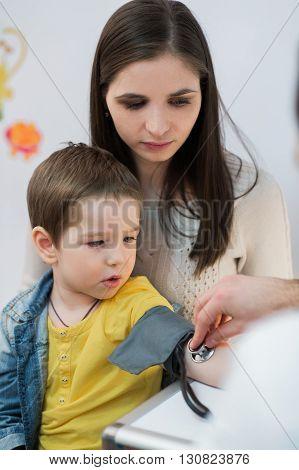 Little boy medical visit - doctor measuring blood pressure of a child.