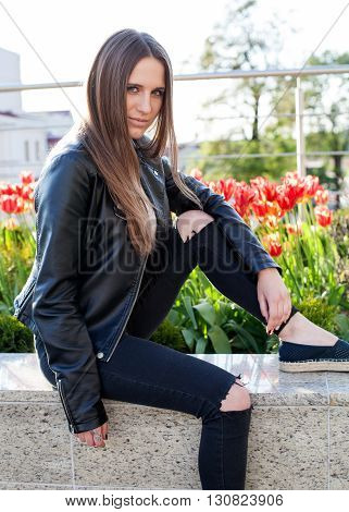 Young woman in black coat and jeans is sitting on the stone parapet in the city red flowers behind her