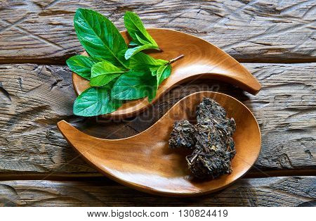 Dried tea with mint in wooden dish on the table