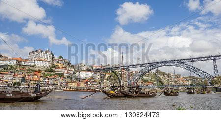 PORTO, PORTUGAL - APRIL 21, 2016: Boat with portwine barrels in front of the Ponte Luis I in Porto, Portugal