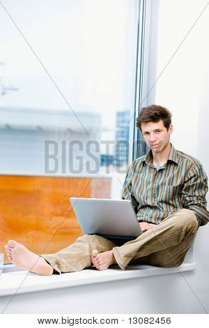 Young casual office worker sitting at office window working on laptop computer.