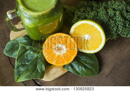 Closeup of spinach, kale and oranges next to a green juice