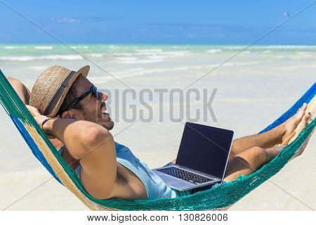 Man working with a laptop, on a hammock in the beach. Concept of digital nomad, remote worker, independent location entrepreneur.