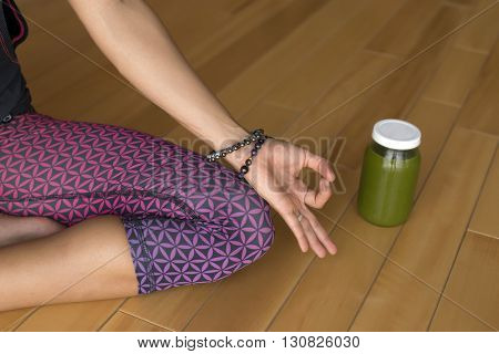 Closeup of a woman's hands during meditation with a green juice