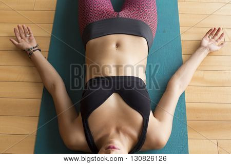 Beautiful woman lying down in her yoga mat during shavasana.