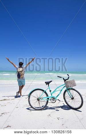 Young traveler in a Caribbean beach with a bike and backpac