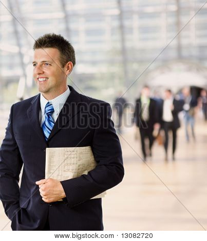 Portrait of happy successful businessman holding newspaper, smiling.