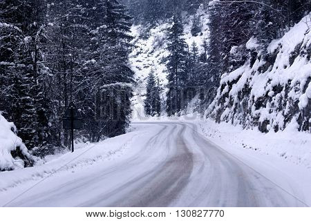 Car driving during winter snow on the Highway
