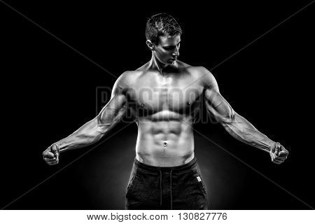 Stunning muscular man showing six pack abs, perfect abs, shoulders, biceps, triceps and chest on black background. Black and white