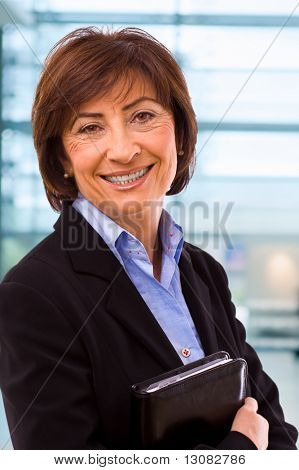 Portrait of senior businesswoman at office lobby.