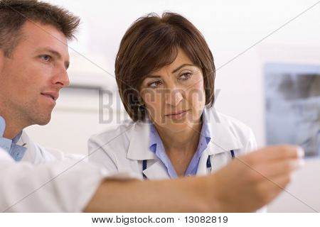 Doctors coworking looking at x-ray image at office.