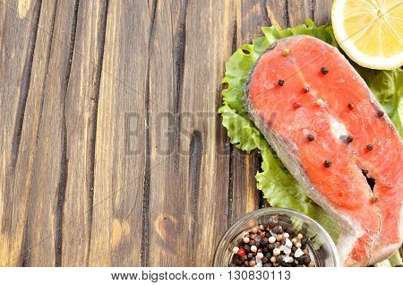uncooked sockeye salmon steak and ingredients background with copy space