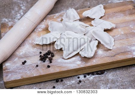 Making of homemade dumplings pastry tortellini or ravioli. Model for home made pasta filled with meat. Preparing organic meal on a wooden desk