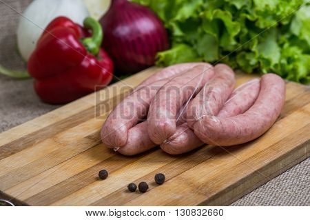 Raw sausages with vegetables on wooden cutting board.