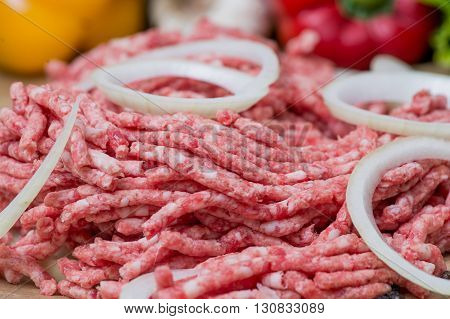 Raw minced meat with onion over fresh vegetables