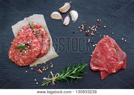 Fresh raw meat and burger cutlets from the farmers market on a black grunge table. Selective focus, flat lay