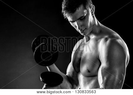 Mighty fitness man showing his gread body with dumbbells in hand on black background.. Black and white. Close up