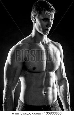 Mighty fitness man showing his gread body with dumbbells in hand on black background. Black and white. Close up