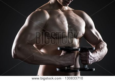 Mighty fitness man showing his gread body with dumbbells in hand on black background. Close up