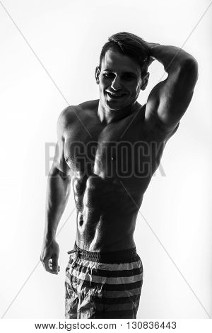 Dark contrast shot of young muscular fitness man stomach and arm. Bodybuilder with beads of sweat training in gym.
