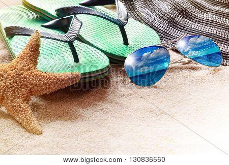 Summer beach. Flip flops starfish and sunglasses on the sand.