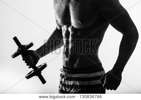 Young strong athlete on dark background isolated