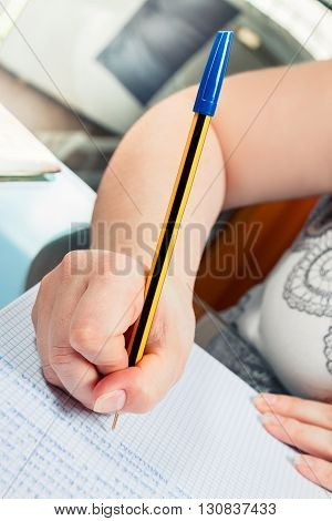 student write on paper with blue pen