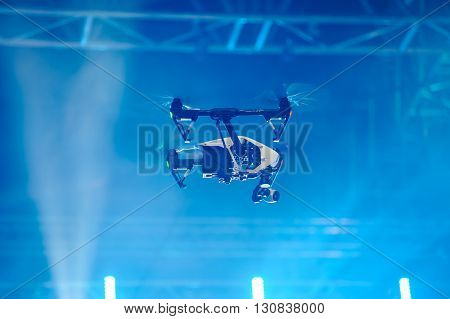 Professional quadrocopter with video camera soars over the stage