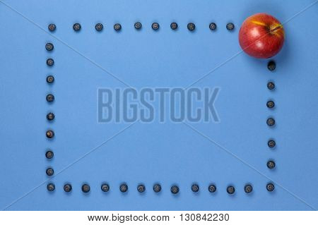 Apple with frame of blueberries on a blue background. It can be used for advertising of healthy nutrition