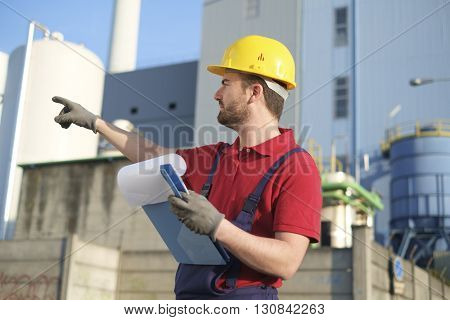 worker with safety helmet outside a factory