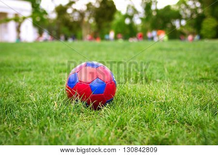 Red and blue fotball on green grass field and peoples at background