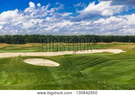 Perfect golf course. Golf club. Green summer golf course landscape with sand bankers. Golf field beautiful landscape with sand traps.