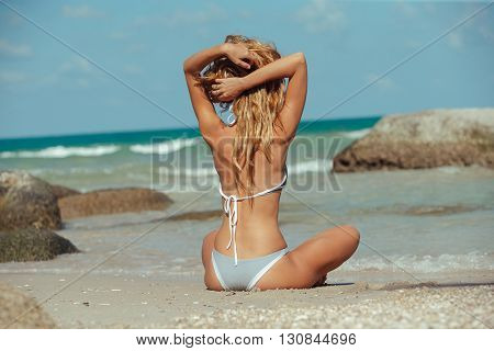 Young adult  girl sitting on tropical beach and looking at see
