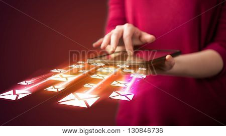 Hand holding tablet and sending email icons concept on background