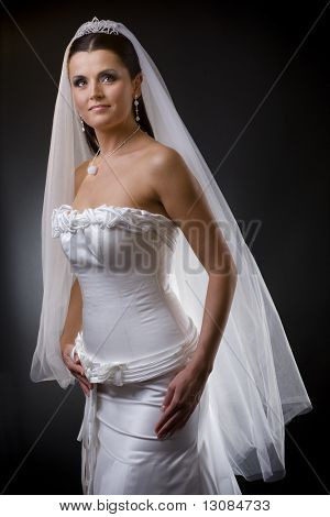 Studio portrait of a young bride wearing white wedding dress with veil, smiling and looking at camera.