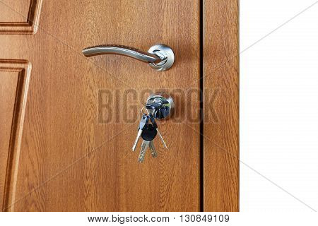 Closed door handle. Door lock with keys. Brown wooden door closeup isolated. Modern interior design, door handle. New house concept. Real estate.