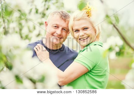 smiling adult couple in love. Blossoming tree garden