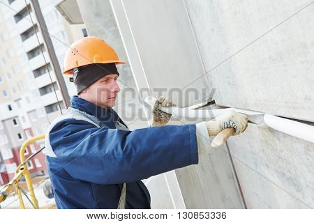 Facade plasterer sealing joint of building wall with putty mastic